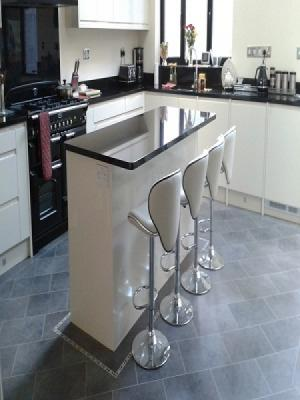 karndean installed in a kitchen with an island laid on the 45° with feature stripping and a mosaic border